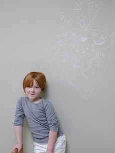 7-8 Year old girl stands below chalk drawing on wallの写真素材 [FYI03635116]