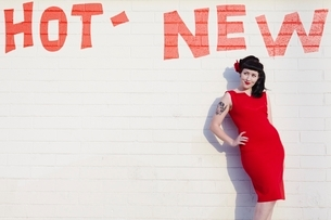 Retro woman in red dress posing against a brick wallの写真素材 [FYI03635158]