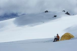 Hiker using laptop outside of tent on snowy mountain peakの写真素材 [FYI03635173]