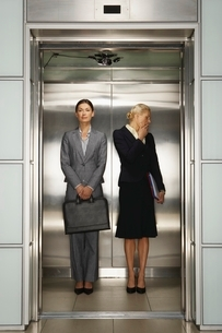 Two Businesswomen in Office Elevatorの写真素材 [FYI03635184]