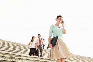 Three office workers walking down steps  woman in foregrouの写真素材 [FYI03635187]