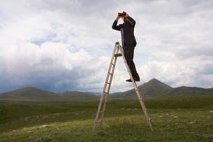 Businessman in mountain field on ladder Looking Through Biの写真素材 [FYI03635200]