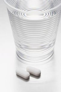 Two pills beside water in plastic cupの写真素材 [FYI03635223]