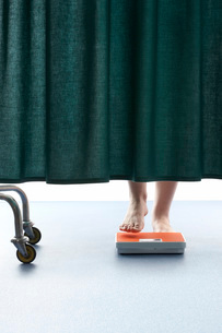 Person stepping onto weighing scales  behind curtain in hoの写真素材 [FYI03635230]