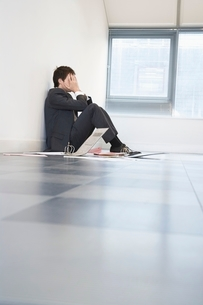 Despaired Businessman Sitting on Floorの写真素材 [FYI03635239]