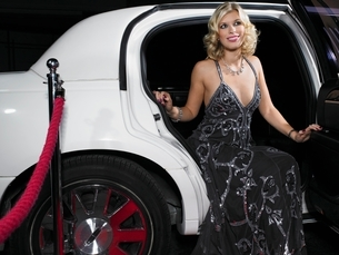 Woman in evening wear getting out of limousineの写真素材 [FYI03635262]