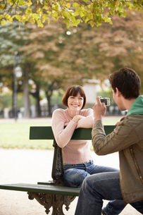 Young man photographing young woman on bench in parkの写真素材 [FYI03635276]