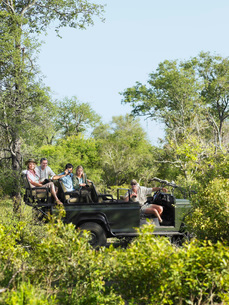 Four tourists and driver in jeep on safari  side viewの写真素材 [FYI03635282]