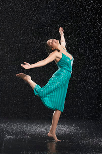 Woman standing on one leg  leaning into falling rainの写真素材 [FYI03635286]