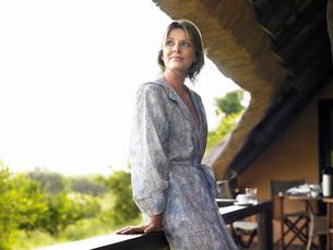 Portrait of adult woman on terrace  in bathrobe  looking oの写真素材 [FYI03635289]