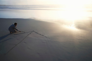 Business man drawing arrow in sand on beach  elevated viewの写真素材 [FYI03635303]