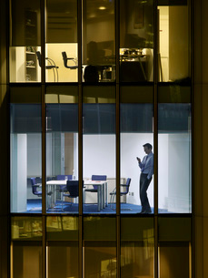 Business man text messaging in office  view from buildingの写真素材 [FYI03635336]