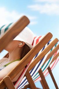 Woman wearing earphones  sitting in deckchair  side viewの写真素材 [FYI03635363]