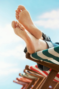 Person resting on deckchair on beach  low section  close uの写真素材 [FYI03635365]