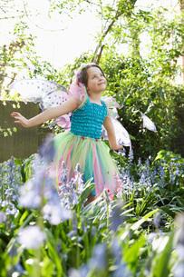 Young girl (5-6) in flower garden wearing fairy costumeの写真素材 [FYI03635376]