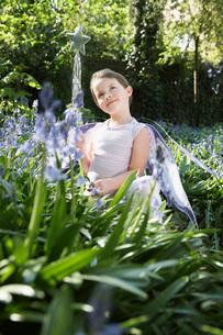 Portrait of young girl (5-6) squatting in flower garden inの写真素材 [FYI03635380]