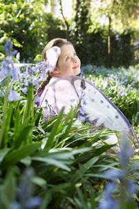 Portrait of young girl (5-6) sitting in flower garden wearの写真素材 [FYI03635381]