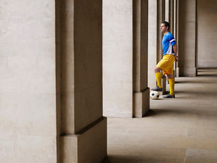 Soccer player holding foot on ball  standing in porticoの写真素材 [FYI03635383]