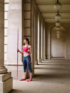 Female athlete holding javelin  standing in portico  portrの写真素材 [FYI03635384]