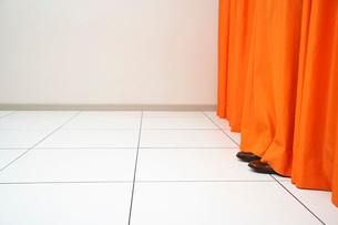 Person hiding behind orange curtainの写真素材 [FYI03635405]