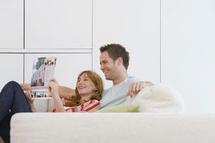 Couple reading brochure on sofaの写真素材 [FYI03635417]
