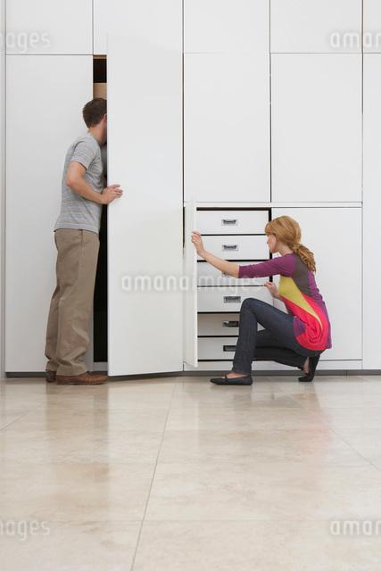 Couple looking in wardrobe in empty apartmentの写真素材 [FYI03635420]