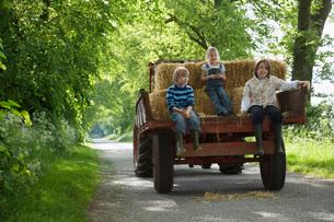 Three children (5-9) sitting on trailer on country laneの写真素材 [FYI03635426]