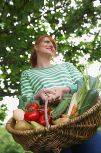 Woman holding fruit and vegetable basket  outdoorsの写真素材 [FYI03635455]