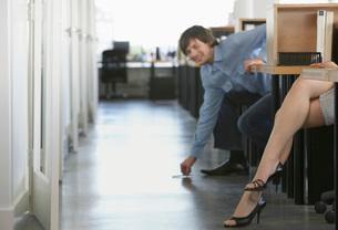 Man picking pen off floor near womans legs in officeの写真素材 [FYI03635485]