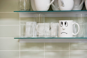Sad face mug on kitchen shelfの写真素材 [FYI03635489]