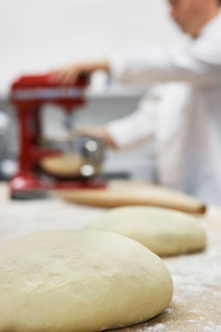 Chef using dough mixer in kitchen  focus on dough in foregの写真素材 [FYI03635523]