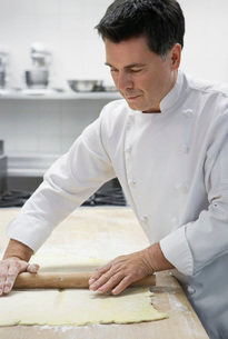 Chef rolling dough in kitchenの写真素材 [FYI03635524]