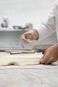 Chef preparing dough in kitchenの写真素材 [FYI03635526]