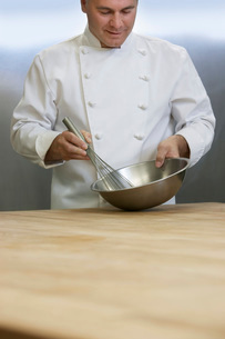 Male chef mixing ingredients using whisk in kitchenの写真素材 [FYI03635536]