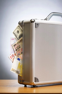 Metal briefcase full of cash on tableの写真素材 [FYI03635574]