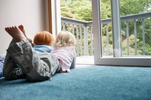 Sisters (3-6) lying on carpet  looking through balcony dooの写真素材 [FYI03635609]