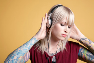 Young tattooed woman listening to music on headphonesの写真素材 [FYI03635691]