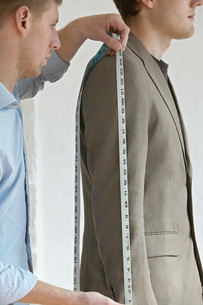 Tailor measuring jacket sleeve on man  side view  close upの写真素材 [FYI03635695]