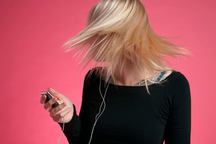 Young woman holding mp3 player and tossing hairの写真素材 [FYI03635697]