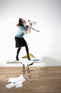 Woman standing on desk  shouting through megaphoneの写真素材 [FYI03635734]