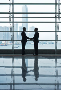 Silhouettes of two business men shaking handsの写真素材 [FYI03635753]