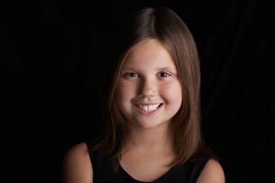 Girl (5-6) on black background  portraitの写真素材 [FYI03635768]