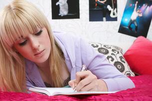 Teenage girl (16-17) lying on bed  writing diaryの写真素材 [FYI03635780]