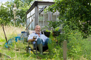 Senior man pouring drink  sitting in gardenの写真素材 [FYI03635809]