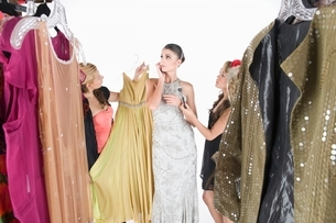 Woman stands ignoring wardrobe assistantsの写真素材 [FYI03635844]