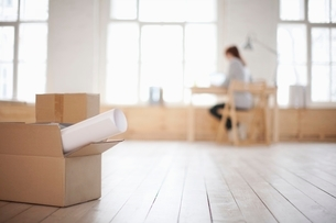 Woman sits at desk in window area of loft apartmentの写真素材 [FYI03635951]
