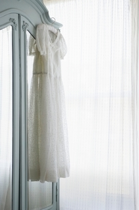 Christening gown on wardrobe at window with net curtainsの写真素材 [FYI03636019]