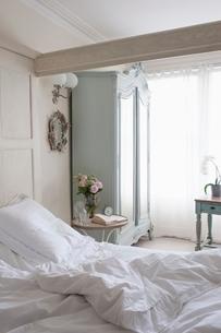 Unmade bed in sunlit beamed roomの写真素材 [FYI03636021]