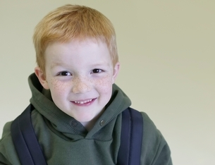 Schoolboy with redhair and freckles stands with backpackの写真素材 [FYI03636041]