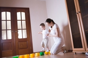 Boy walks along building blocks with help from his motherの写真素材 [FYI03636042]